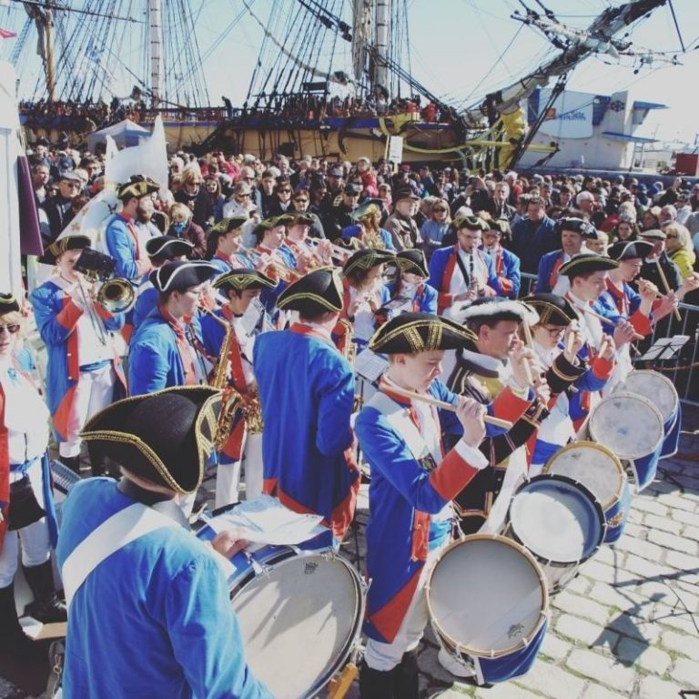 Parade with musical instruments and mariners costumes with a tall ship
