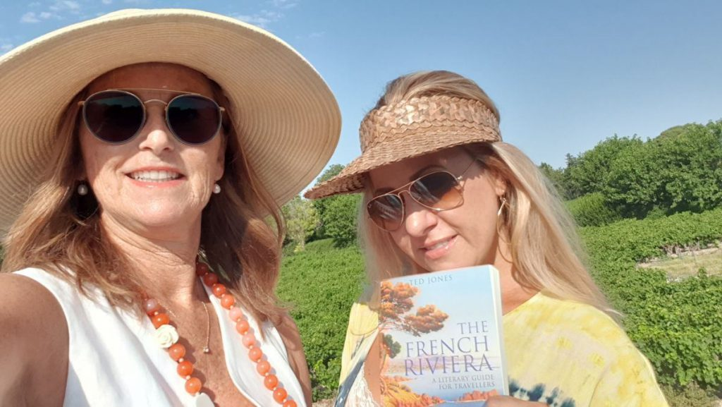 Two women with sunglasses and hats in front of a vineyard holding a book the French Riviera by Ted Jones