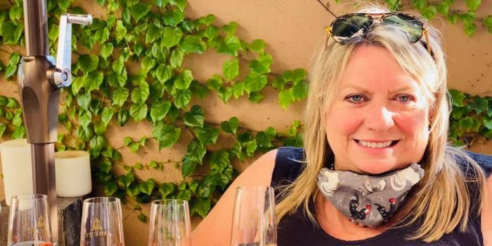 Cheryl Jamison with rooster mask with 4 glasses tating wine on a sunny day outdoors
