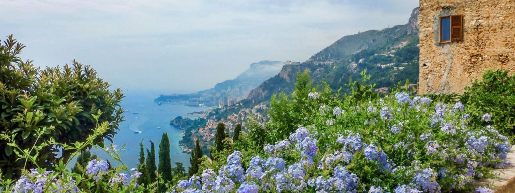 Mediterranean bay, cliffs with villages, an old stone house and purple flowers