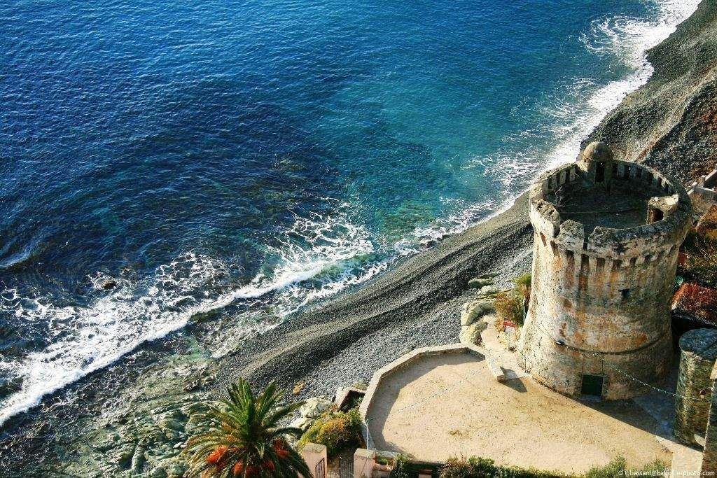 An ancient tower by a beach with sand, palm trees and mediterranean sea