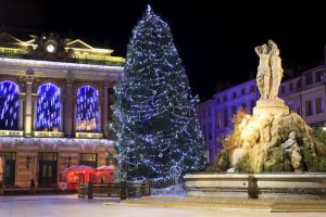 A fountain lit with 3 statues , christmas tree and and a historic opera house in Montpellier Comedie Square