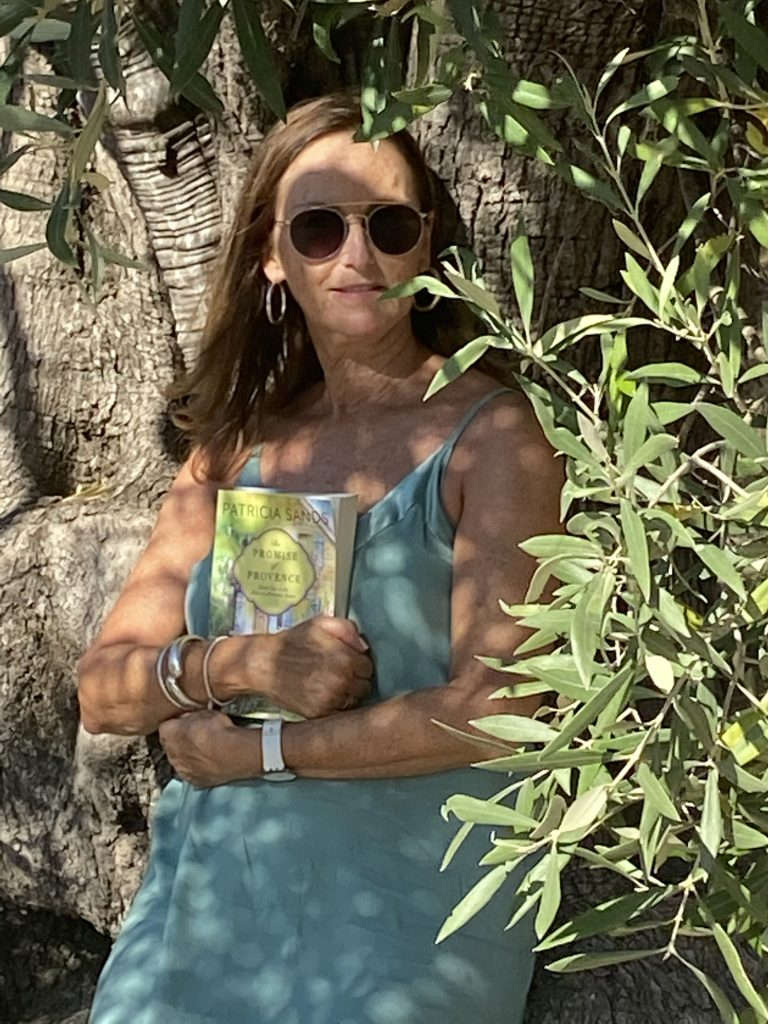 WOMAN IN BLUE DRESS IN OLIVE GROVE HOLDING BOOK PROVENCE PATRICIA SANDS